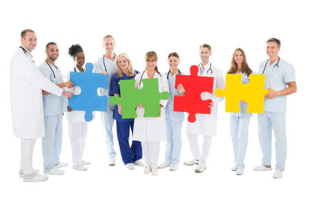 Full length portrait of confident medical team holding jigsaw pieces against white background Stock Photo