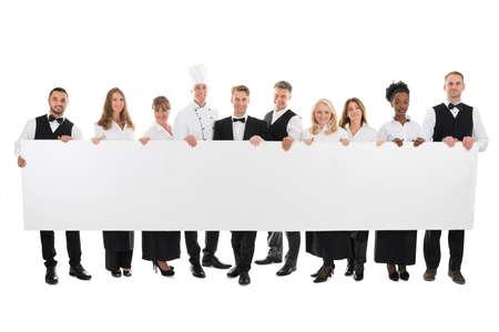 hospitality staff: Portrait of confident restaurant staff holding blank billboard against white background Stock Photo