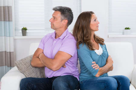 hurt: Unhappy Mature Couple With Armcrossed Sitting On Sofa After Quarrel