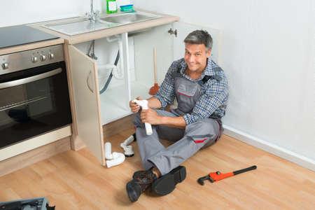 plumber: Longitud total de fontanero madura reparación de la tubería del fregadero en la cocina