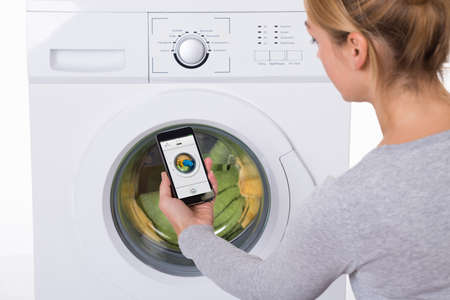 Rear view of young woman using mobile phone to operate washing machine against white background