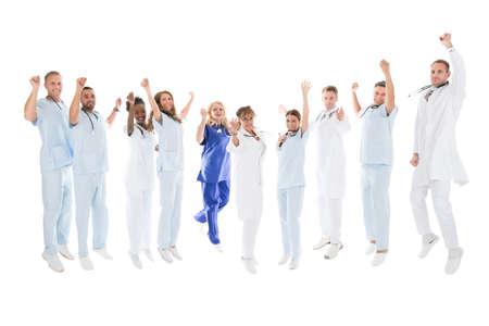personas saltando: Retrato de cuerpo entero de equipo médico multiétnica de pie con los brazos en alto contra el fondo blanco