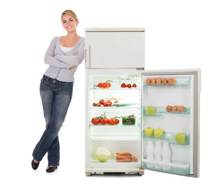 refrigerator: Portrait of confident young woman leaning on open refrigerator over white background