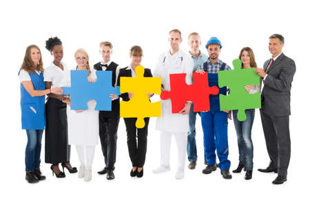 occupations: Portrait of confident people with various occupations holding jigsaw pieces while standing against white background