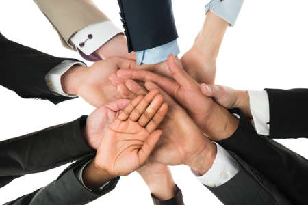 directly below: Directly below shot of business team stacking hands against white background