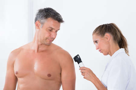 man doctor: Female Doctor Examining Pigmented Skin Of Patient With Dermatoscope Stock Photo