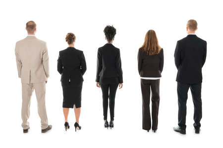 personas de pie: Full length rear view of business team standing against white background