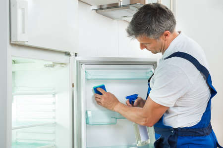 refrigerator: Side view of mature janitor cleaning refrigerator with spray bottle and sponge at home