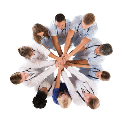 collaborate: Directly above shot of multiethnic medical team stacking hands against white background
