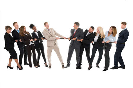 Full length of multi ethnic business teams playing tug of war against white background Foto de archivo