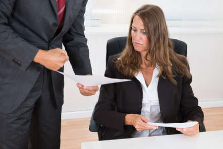 intimidation: Close-up Of Businessman Showing Document To Female Employee In Office Stock Photo