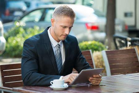 cafe internet: Retrato de un hombre de negocios que usa la tablilla digital
