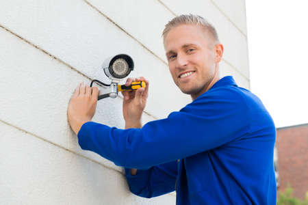 seguridad en el trabajo: Sonriendo Joven Técnico Instalación de la cámara en la pared con destornillador