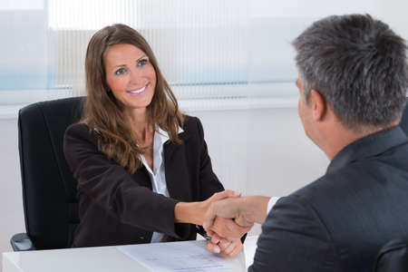career: Happy Businesswoman Shaking Hands With Businessman In Office
