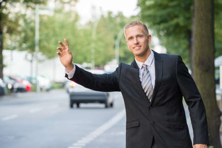 businessman waiting call: Close-up Of Businessman Trying To Call For Taxi Stock Photo