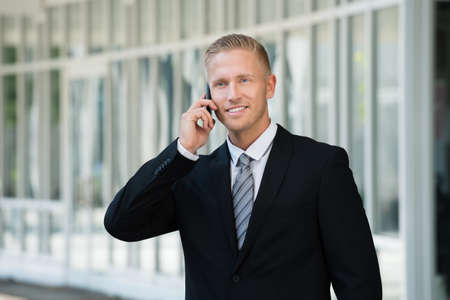 standing businessman: Photo Of Happy Young Businessman Talking On Cellphone