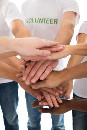 team hands: Midsection of multiethnic volunteers piling hands against white background