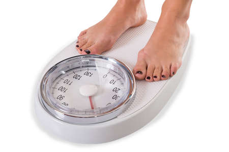 low scale: Low section of woman standing on weighing scale over white background