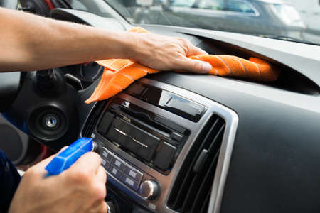 Bijgesneden afbeelding van volwassen mannelijke werknemer reiniging autodashboard Stockfoto