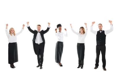 hospitality staff: Full length portrait of happy waiter and waitresses standing with arms raised over white background