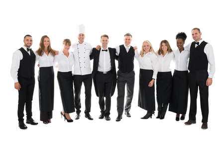 hospitality staff: Full length portrait of confident restaurant staff standing with arms around against white background