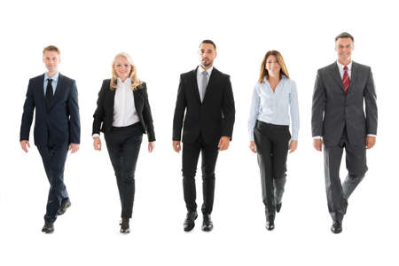 BUSINESSMEN: Full length portrait of confident business people walking against white background Stock Photo