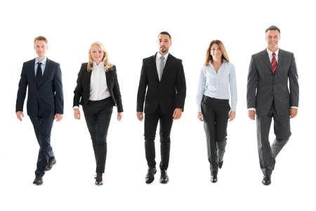 Full length portret van vertrouwen in mensen uit het bedrijfsleven lopen tegen een witte achtergrond