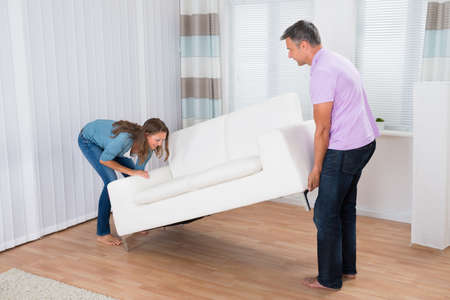 couple on couch: Couple Trying Hard To Move A Couch To Their New Apartment