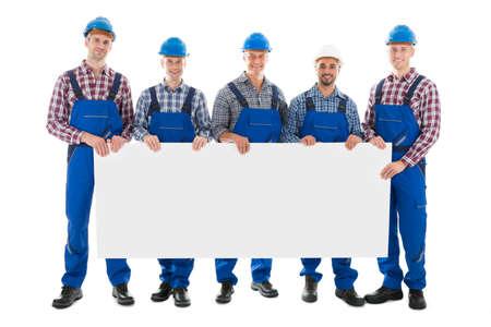 白い背景に、ブランクの看板を持って自信を持って男性建設作業員の完全な長さの肖像画