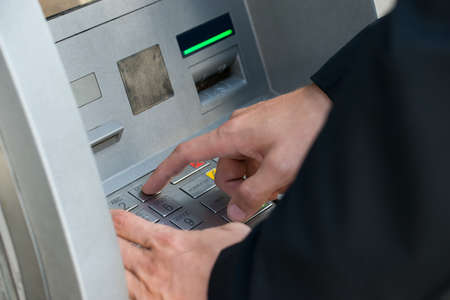 withdraw: Person Using Keypad Atm Machine To Withdraw Money