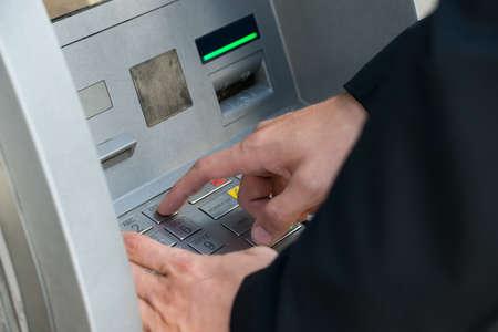 automatic transaction machine: Persona que usa la máquina del teclado cajero automático para retirar dinero