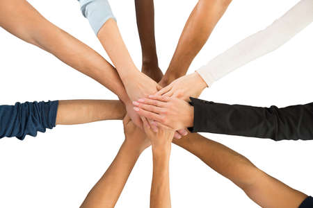 piling: Directly above shot of creative business team piling hands against white background
