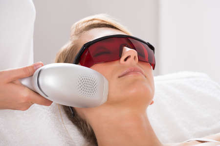 treatment: Closeup of young woman undergoing laser treatment at salon Stock Photo