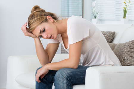 Mulher forçada nova sentado na sala de estar em casa Imagens