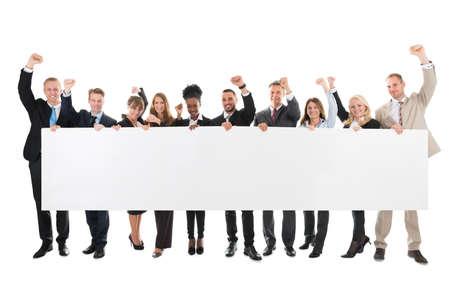 Retrato de cuerpo entero de equipo de negocios con los brazos levantados que sostiene la cartelera en blanco sobre fondo blanco