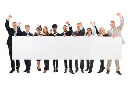 Full length portrait of business team with arms raised holding blank billboard against white background Stockfoto