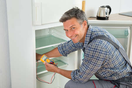 electrical appliances: Mature male technician checking fridge with digital multimeter at home