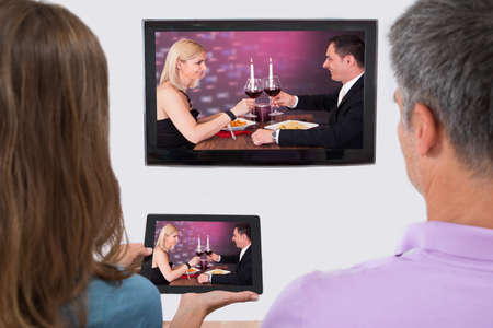 television screen: Rear View Of Couple Connecting Television Channel Through Wifi On Digital Tablet
