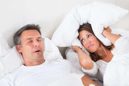 pareja durmiendo: Mujer que cubre sus oídos con la almohada Mientras que el hombre que ronca