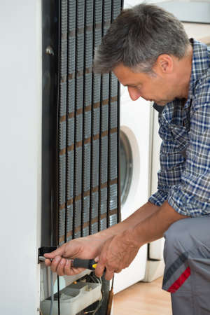 cropped image: Cropped image of serviceman working on fridge with screwdriver at home