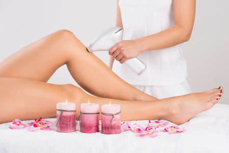 lasers: Low section of young woman getting laser treatment on leg at spa Stock Photo