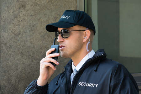 police radio: Portrait Of Young Security Guard Using Walkie-talkie Radio Stock Photo