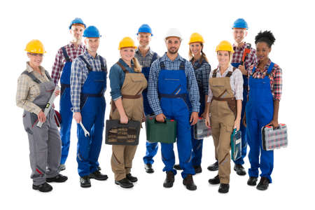 Full length portrait of confident carpenters carrying toolboxes against white background Foto de archivo