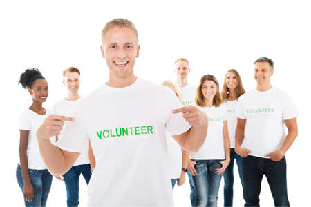 group cooperation: Portrait of happy man showing volunteer text on tshirt with friends standing over white background
