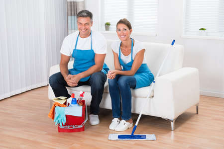man sit: Two Happy Cleaners Sitting On Couch In Living Room
