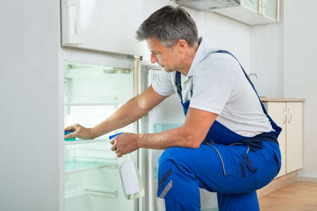 home appliances: Side view of mature janitor cleaning refrigerator with spray bottle and sponge at home