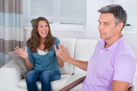conflicto: Mujer madura se sienta en el sofá que discute con el hombre en el hogar Foto de archivo