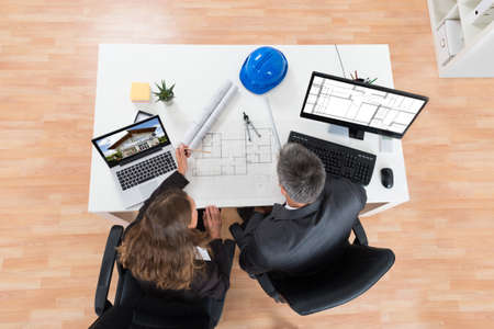 architectural architect: High Angle View Of Two Architects Discussing Blueprint In Office Stock Photo
