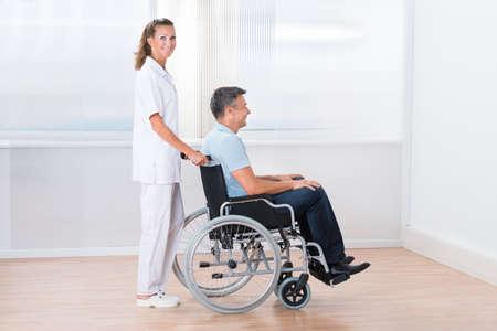 persona en silla de ruedas: Sonreír Doctora empuja al paciente para discapacitados que se sienta en silla de ruedas en el hospital