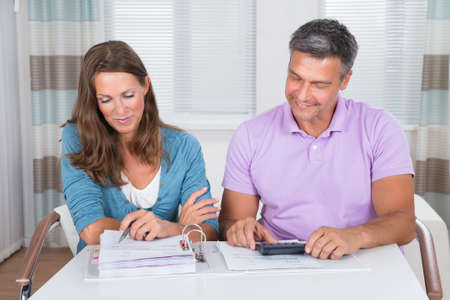 bills: Mature Couple Sitting At Home Calculating Bills